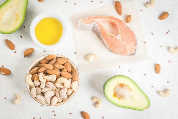Gezond eten. producten met gezonde vetten. omega 3, omega 6. ingrediënten en producten: forel (zalm), lijnzaadolie, avocado, amandelen, cashewnoten, pistachenoten. op een witte stenen tafel. kopieer ruimte bovenaanzicht