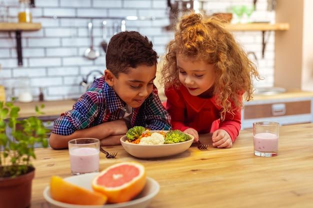 Gezond eten. raadselachtige jongen die op tafel leunt terwijl hij gaat eten