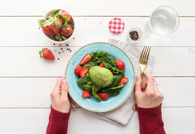 Gezond eten. salade met aardbeien, avocado's, spinazie op een witte houten achtergrond bovenaanzicht plat lag