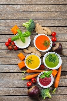 Gezond eten, schoon eten concept. verscheidenheid aan kleurrijke seizoensgebonden herfstgroenten romige soepen met ingrediënten. pompoen, broccoli, wortel, rode biet, aardappel, tomatenspinazie. plat leggen, ruimte kopiëren