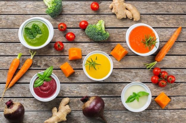 Gezond eten, schoon eten concept. verscheidenheid aan kleurrijke seizoensgebonden herfstgroenten romige soepen met ingrediënten. pompoen, broccoli, wortel, rode biet, aardappel, tomatenspinazie. plat leggen