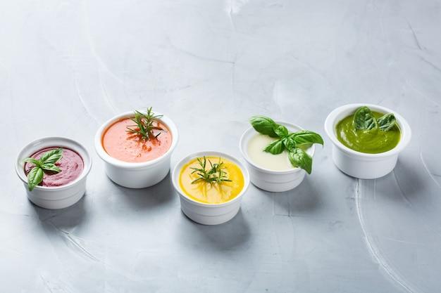 Gezond eten, schoon eten concept. verscheidenheid aan kleurrijke seizoensgebonden herfstgroenten romige soepen met ingrediënten. pompoen, broccoli, wortel, rode biet, aardappel, tomatenspinazie. ruimte kopiëren