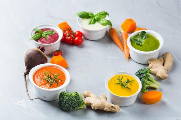 Gezond eten, schoon eten concept. verscheidenheid aan kleurrijke seizoensgebonden herfstgroenten romige soepen met ingrediënten. pompoen, broccoli, wortel, rode biet, aardappel, tomatenspinazie