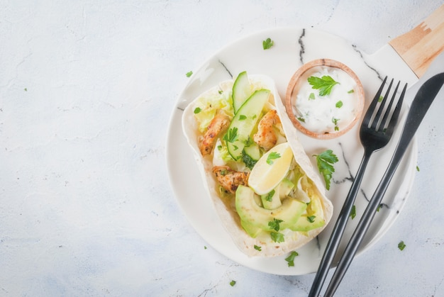 Gezond eten snack. tortillas taco met gegrilde kip, avocado, verse salsa, sla, limoen. met yoghurt & peterselie saus. op lichtgrijze stenen marmeren tafel, marmeren plaat. kopieer ruimte bovenaanzicht