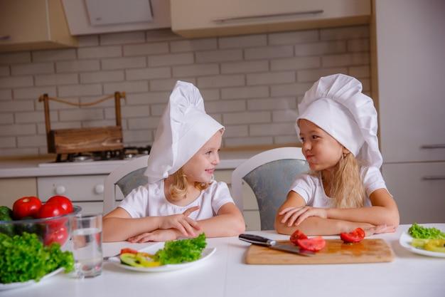 Gezond eten thuis. gelukkige familie in de keuken. twee schattige grappige kinderen bereiden de groenten voor.