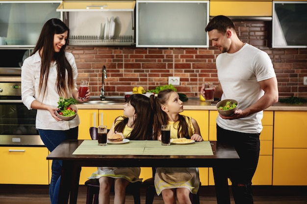 Gezond eten versus slechte gewoonten. ouders bieden hun dochters een salade met sap aan in plaats van een burger en frisdrank. kleine meisjes zijn niet gelukkig. junk food concept