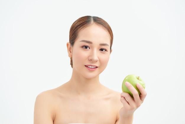 Gezond eten, voeding en mensenconcept - glimlachende jonge vrouw met groene appel thuis