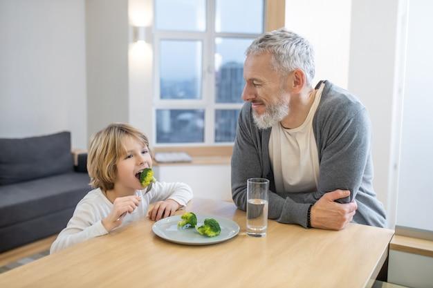 Gezond eten. volwassen man en zijn zoon samen aan het ontbijt