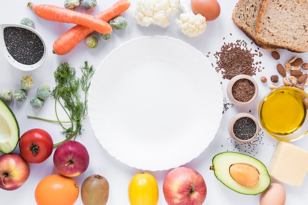 Gezond fruit; groenten; droge vruchten; brood; zaden en kaas; ei; olie; met lege plaat op witte achtergrond