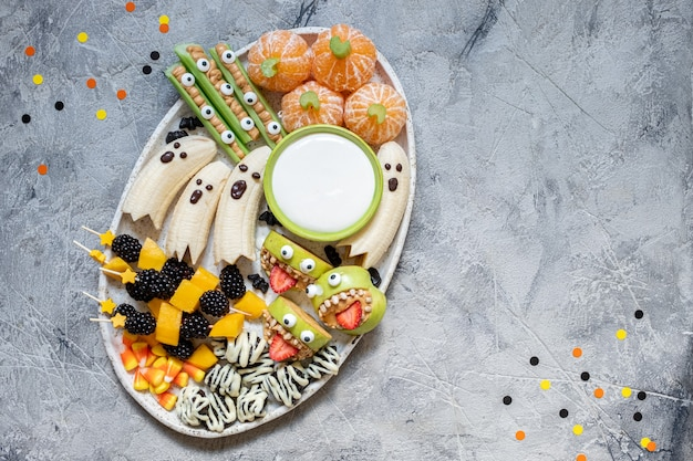 Gezond fruit halloween-traktaties. banana ghosts, clementine orange pumpkins en apple monster mounts
