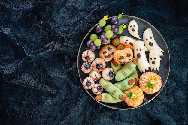 Gezond fruit halloween-traktaties. banana ghosts, clementine orange pumpkins, lychee eyes en green witch fingers cookies