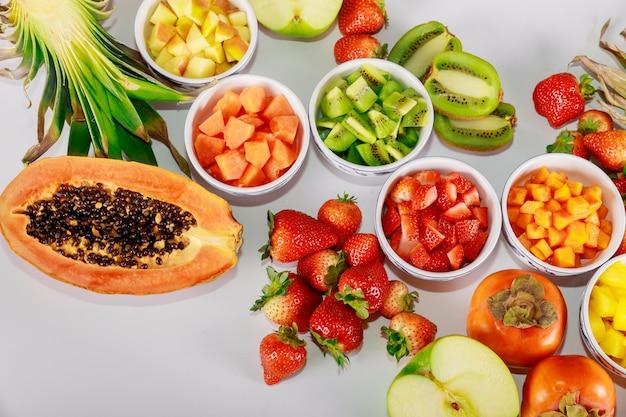 Gezond fruit. salade maken van papaja, aardbei, appel, ananas, kiwi en persimmon.