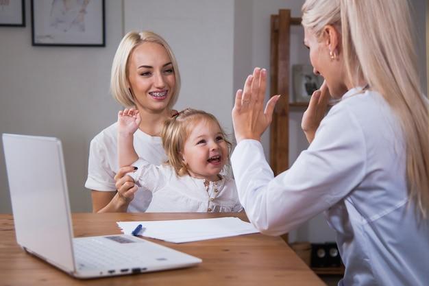Gezond gelukkig kindmeisje dat high five geeft aan vrouwelijke zorgzame arts. vier goed medisch resultaat, kinderarts met kind patiënt goede relatie vertrouwen concept