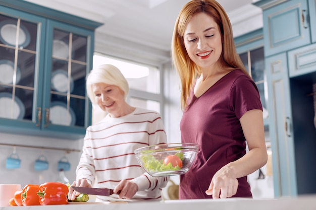 Gezond gerecht. charmante jonge vrouw en haar bejaarde moeder die samen een salade maken, waarbij de jongere vrouw een kom met groenten vasthoudt terwijl de oudere aan het snijden is