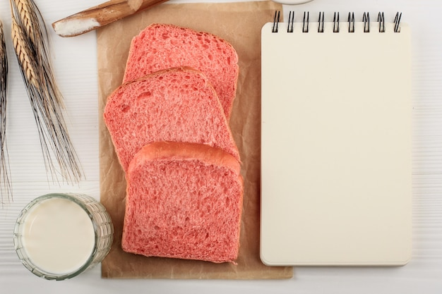 Gezond gesneden roze brood naast blanco open boek voor kookboek, recept voor tekst of advertentie. concept voor dieetplanning op nieuwjaar 2021. bovenaanzicht