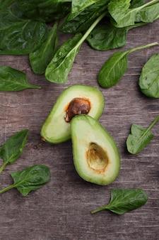 Gezond groen groente: spinazie, komkommer, sla, appel en avocado op donkere achtergrond. plat leggen, ruimte kopiëren.