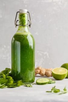Gezond groen plantaardig detoxsap in een glasfles. veganistische komkommer, peterselie groen sap. kopieer ruimte