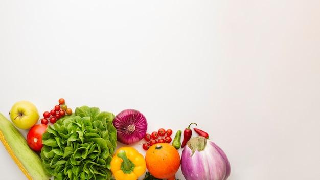 Gezond groentenhoogtepunt van vitaminen op witte achtergrond met exemplaarruimte