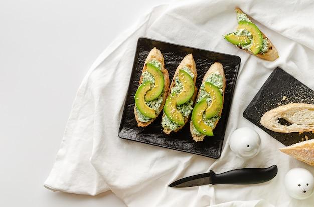 Gezond heerlijk ontbijt met open sandwiches gemaakt van stokbrood, ricotta, spinazie en avocado op zwarte plaat op witte tafel. kopieer ruimte