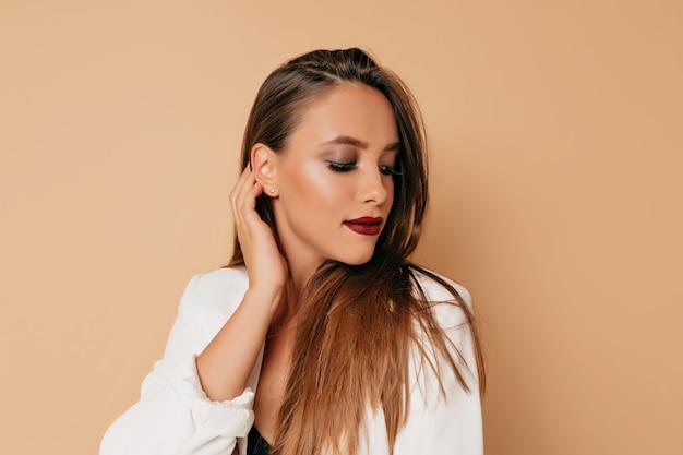 Gezond huid vrouwelijk concept, mooie vrouw met wijnstoklippen en donkere ogen die witte jas dragen die op beige muur stellen. jonge vrouw lachend natuurlijk portret, mooi vrouwelijk meisje met lang haar