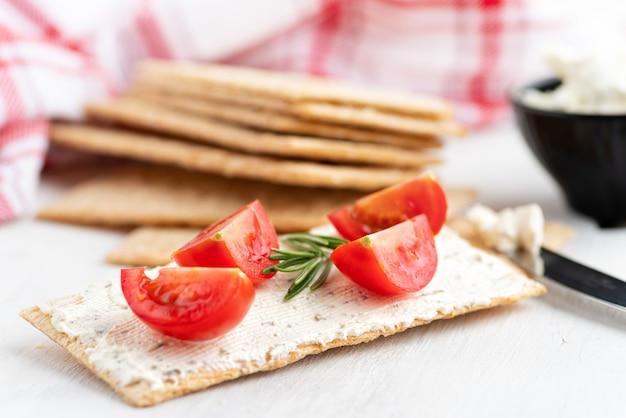 Gezond knapperig roggebrood met zachte kaas, bieslook en kerstomaatjes selectieve aandacht op een lichte achtergrond. gezond ontbijt. kopieer ruimte