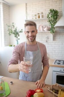 Gezond leven. een glimlachende man met een glas water in de ochtend
