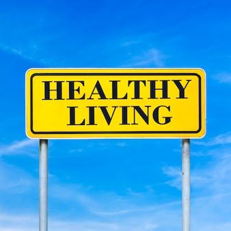 Gezond leven geschreven op gele straatnaambord over blauwe hemel.