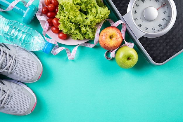Gezond levensstijl, voedsel en sportconcept op groene pastelkleurachtergrond.
