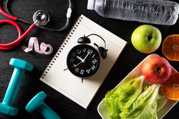 Gezond levensstijl, voedsel en sportconcept op zwarte achtergrond.