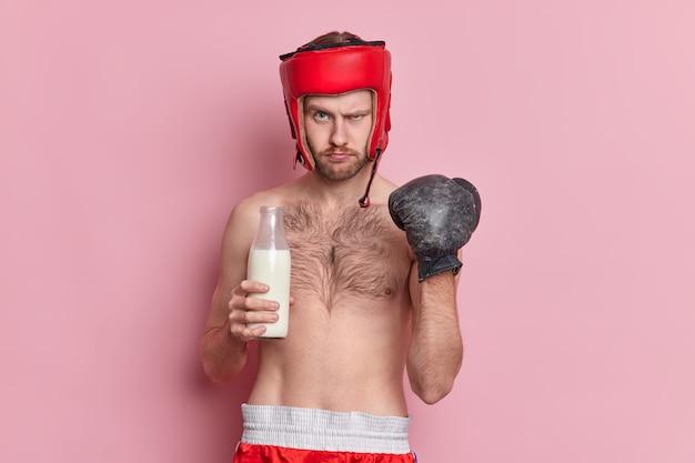 Gezond levensstijlconcept. ernstige mannelijke bokser met naakte torso balt vuist in bokshandschoen vertelt over voordelen van melk voor sporters trekt wenkbrauwen op en heeft strikte uitdrukking