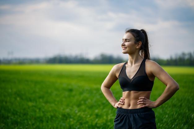 Gezond levensstijlconcept. jonge aantrekkelijke vrouw in sportkleding strekt haar hand uit voordat ze bij zonsopgang op de natuur traint. spier opwarming