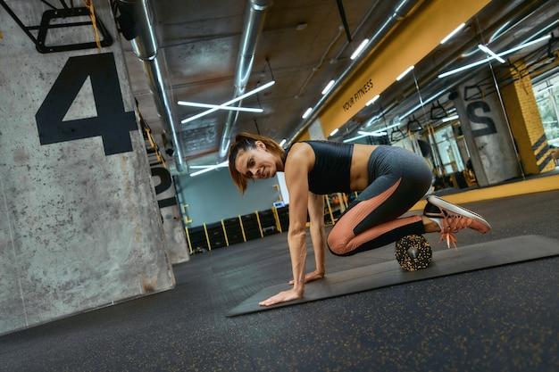 Gezond levensstijlconcept. jonge mooie sportieve vrouw in sportkleding trainen met speciale fitnessapparatuur op sportschool, met behulp van schuimroller. sportieve mensen, trainings- en trainingsconcept