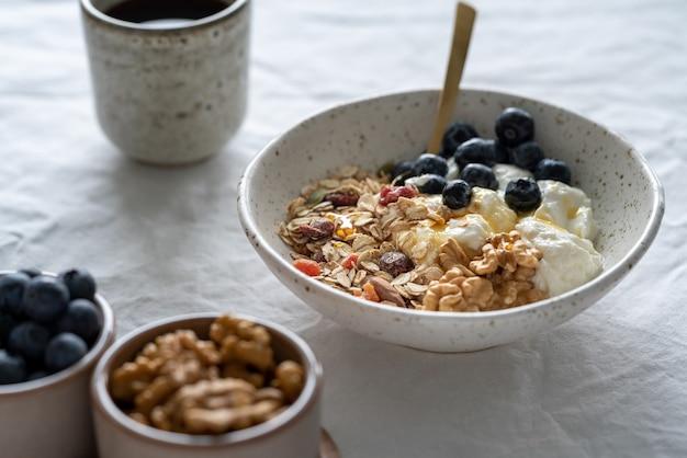 Gezond levensstijlontbijt met muesli van muesli en yoghurt in kom op witte lijstlijst