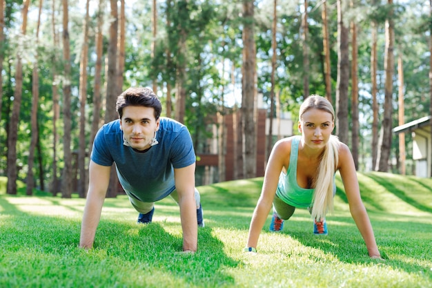 Gezond lichaam. leuke jonge mensen die push-ups doen terwijl ze aan hun spieren werken