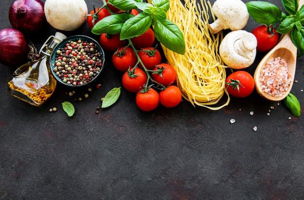 Gezond mediterraan dieet met spaghetti, tomaten, basilicum, olijfolie, knoflook, paprika op zwarte ondergrond