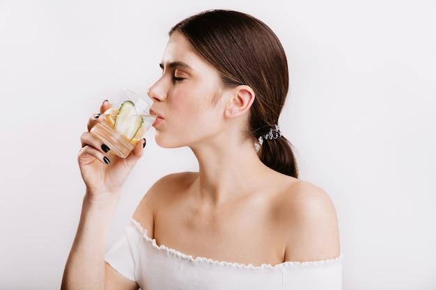 Gezond meisje met heldere huid drinkt in de ochtend water met citroen en komkommer. schot van mooi model zonder make-up op witte muur.