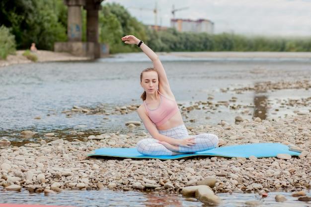 Gezond meisje ontspannen tijdens het mediteren en het doen van yoga-oefeningen in de prachtige natuur aan de oever van de rivier.