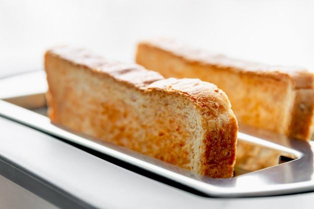 Gezond modevoedsel van ontbijt. roosteren in een broodrooster. broodrooster met smakelijke ontbijttoosts op de lijst