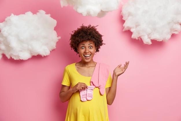 Gezond moederschap en zwangerschap concept. vrolijke jonge toekomstige moeder kijkt graag en gebaren met aarzeling, anticipeert op babymeisje, roze kleine sokken en romper koopt, geeft uitdrukking aan geluk