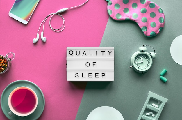 Gezond nacht slaap creatief concept. slaapmasker, wekker, koptelefoon, oordopjes, kalmerende thee en pillen. split two tone roze en groen