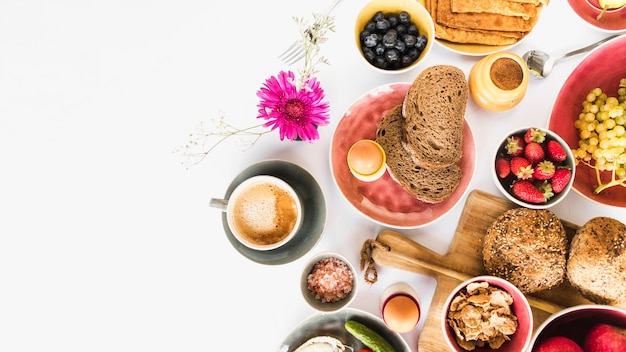 Gezond ochtendontbijt met vruchten en thee op witte achtergrond