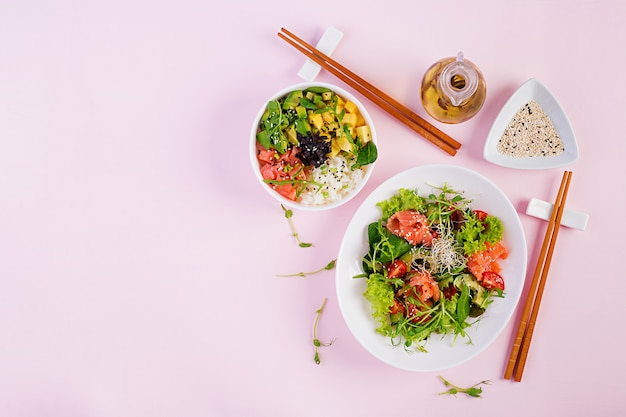 Gezond ontbijt. boeddha schaal met rijst, mango, avocado en zalm en frisse salade met tomaten, avocado, rucola, zaden, zalm. gezond eten concept. bovenaanzicht. plat liggen
