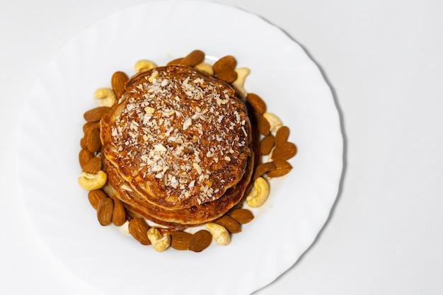 Gezond ontbijt, bovenaanzicht van zelfgemaakte amerikaanse veganistische pannenkoeken met rauwe cashewnoten en amandelnoten in witte plaat.