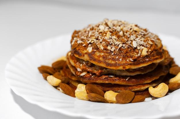 Gezond ontbijt, close-up van zelfgemaakte amerikaanse veganistische pannenkoeken met rauwe cashewnoten en amandelnoten in witte plaat.