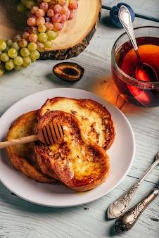 Gezond ontbijt concept. franse toast met honing, fruit en thee over witte houten tafel