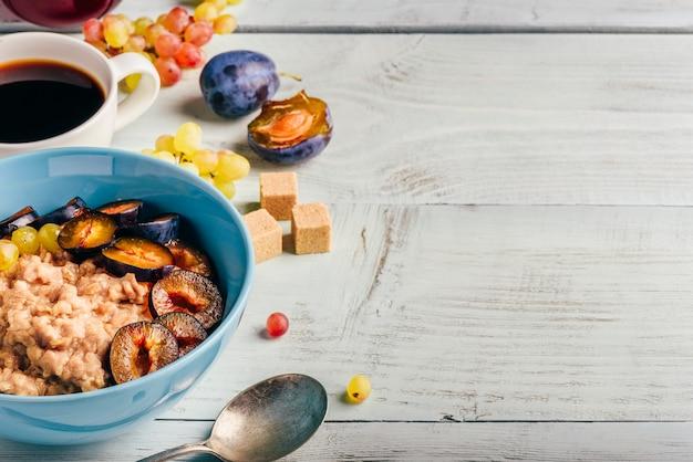 Gezond ontbijt concept. pap met verse pruimen, groene druiven en kopje koffie.