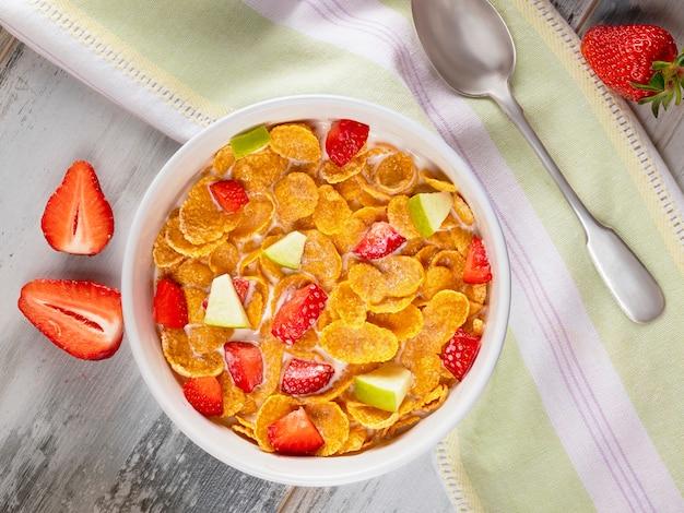 Gezond ontbijt cornflakes en aardbeien met melk en sinaasappelsap.