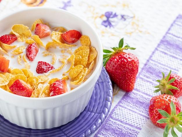 Gezond ontbijt cornflakes en aardbeien met melk