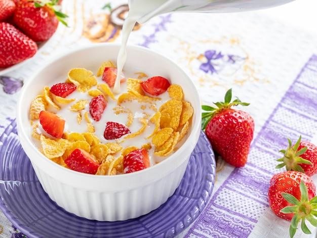 Gezond ontbijt cornflakes en aardbeien met melk.