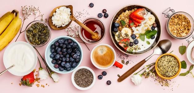 Gezond ontbijt dat met koffie en granola wordt geplaatst